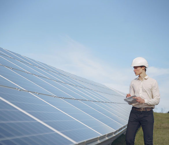 man looking at solar panels wearing a hard hat